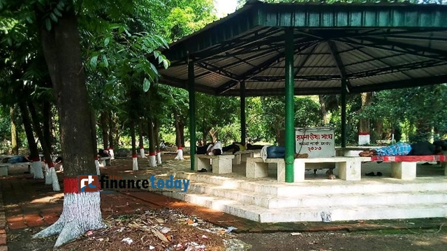 People are seen deep asleep on the bench slabs under trees at Ramna Park in the capital on Thursday. Photo: Nirmal Barman